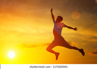 a young man jumps to the top on the background of the sunset