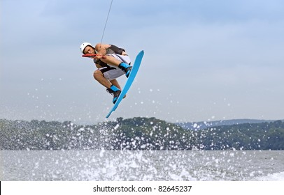 A young man jumps the wake behind a boat.