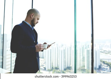 Young man jurist is reading the new bill in internet via mobile phone during coffee break in work day. Male skilled CEO is watching video on cell telephone, while is resting after meeting with clients