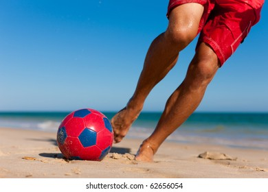 Young man (just feet) on the beach playing soccer in his vacation, he is about to kick the ball