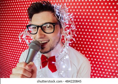 Young man at a karaoke party with christmas lights