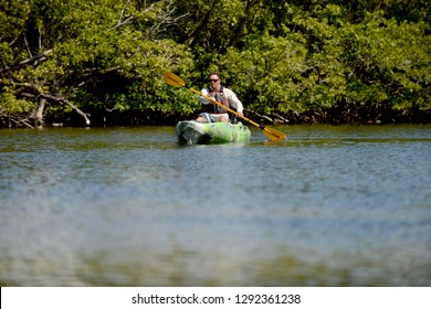 Young man kayaking in florida flats among the mangrove trees