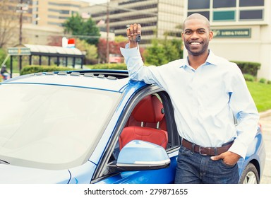 Young man with the keys standing by his new car