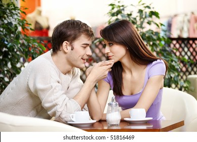 Young man kisses a hand to the beautiful girl on cafe