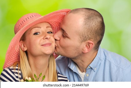Young man kissing attractive woman on green background.