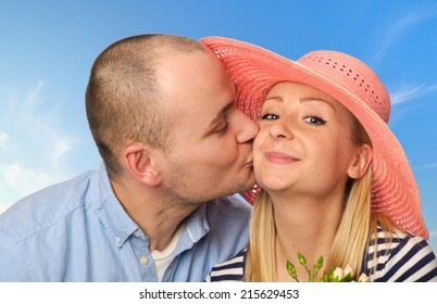 Young man kissing attractive woman on blue sky.