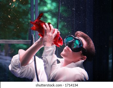Young man kissing fish underwater