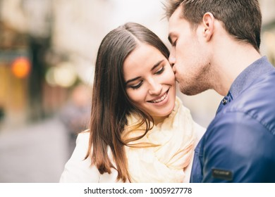 Young man kissing girlfriend on street