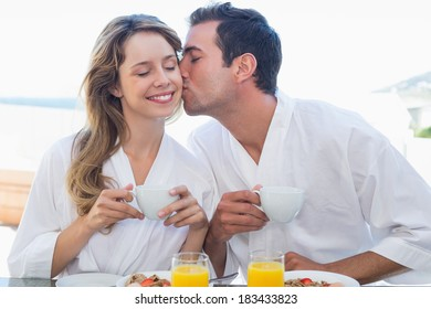 Young man kissing happy woman at breakfast table at home