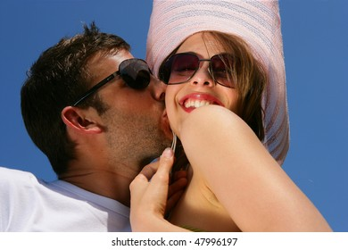 Young man kissing his girlfriend on the cheek