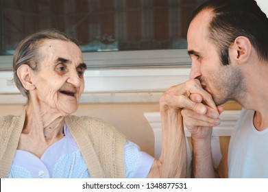 Young man kissing his grandmother's hand, showing his love, respect and gratitude.
