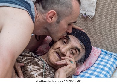 Young man kissing his grandmother's face, showing his love, respect and gratitude.