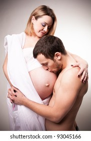Young man kissing his preganant wife belly