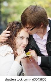 Young man kissing woman forehead closeup photo