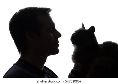 A young man with a kitten in his hands - silhouette