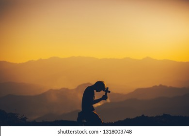 Young man kneeling down praying and holding christian cross for worshipping God at sunset background. christian silhouette concept.