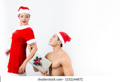 young man kneeling on her back girlfriend and hands her a spacial gift,Woman wearing chrismas suit is pleased with man wear chrismas hat,Couple in chrismas day,