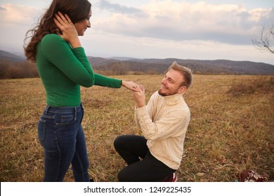 "Young man kneeling proposing to young woman, his fiancee. Romantic couple age range of 20-29 years old, alone on mountain hill, in yellow Autumn grass field. National park ""Fruska Gora"" in Serbia."