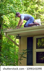Young man kneels at the edge of his roof and reaches in to clean the leaves out of the gutters surrounding the roof of his house.