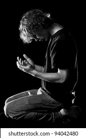 A young man kneels and prays