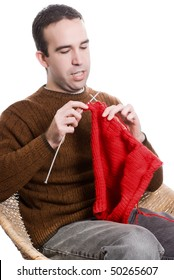 A young man knitting a red cloth, isolated against a white background