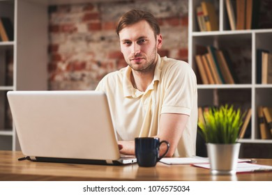 Young man with a laptop - Shutterstock ID 1076575034