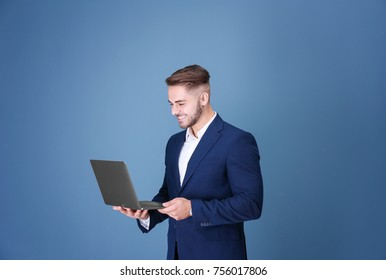 Young man with laptop against blue background