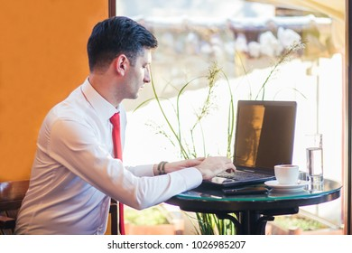 Young man with laptop in cafe.