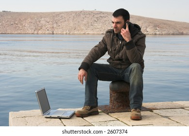 young man with laptop and cell phone