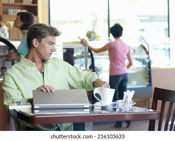 Young man with laptop computer in cafe, looking at watch