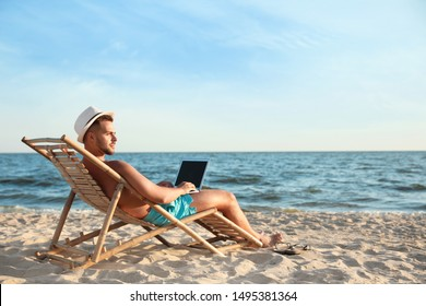 Young man with laptop in deck chair on beach