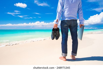 Young man with laptop during tropical beach vacation