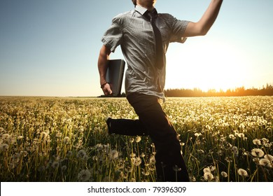 Young man with laptop in hand running on meadow with dandelions