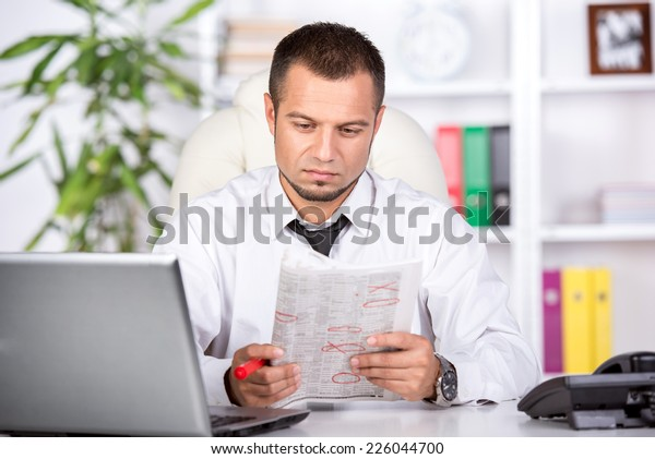 Young man with laptop and newspaper at the table is looking for a job.