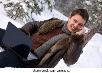 young man with laptop outdoors talking mobile phone