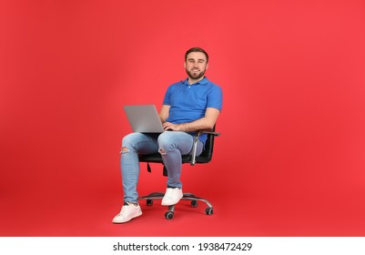 Young man with laptop sitting in comfortable office chair on red background
