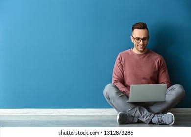 Junge Mann mit Laptop in der Nähe der farbigen Wand