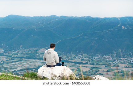 Young man with laptop sitting on top if mountain working online. Cellular network broaband coverage concept. 5G.