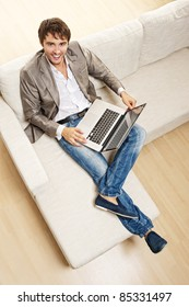 Young man with a laptop sitting on a sofa.