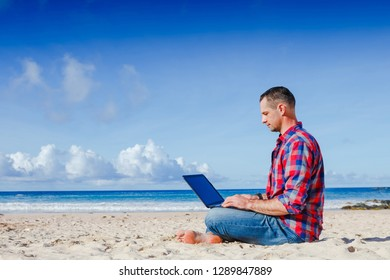 Young man with laptop working on the sand beach