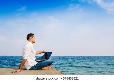 Young man with laptop working on seaside