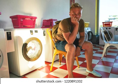 A young man in the Laundromat sits on a chair and waits for the completion of washing. Room with laundry machines, Sunny summer day.