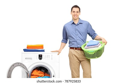 Young man with a laundry basket next to a washing machine isolated on white background