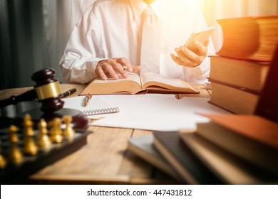 Young man lawyer give suggestion mobile customer and reading the lawyer book for legislation issue to help afflicted people, front view photography with vintage picture style and sunlight effect.