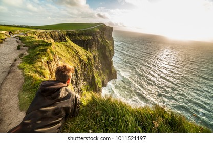 Young man laying down on the edge of the cliffs on the Coastal footpath walk, Cliffs of Moher, huge sea cliffs located at the southwestern edge of the Burren region in County Clare, Ireland.