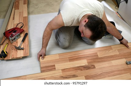 Young man laying the floor panels