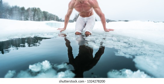 Young man with lean muscular body going to swim in the cold winter water with ice floating on the surface and forest on the background. Tilt shift effect applied, focus on the floating ice pieces