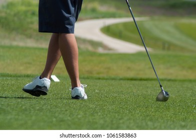 Young man leaning on his golf club on the putting green wearing blue shorts and white golf shoes. Playing golf in the summertime on a golf course.