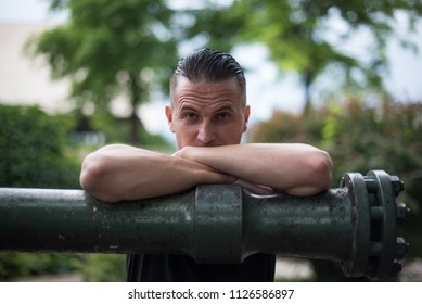 young man leaning on pipe