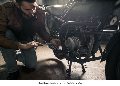 Young man in leather jacket fixing motorcycle
